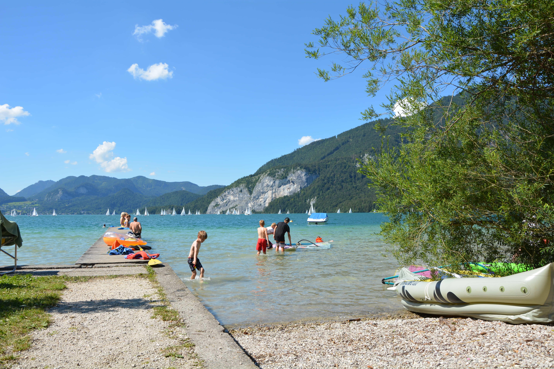 """Blick vom Campingplatz """"Seecamping Primus"""" im Salzkammergut auf den Wolfgangsee. Liks im Bild der Badesteg, im Hintergrund die Berge. Im Wasser einige Badegäste."""