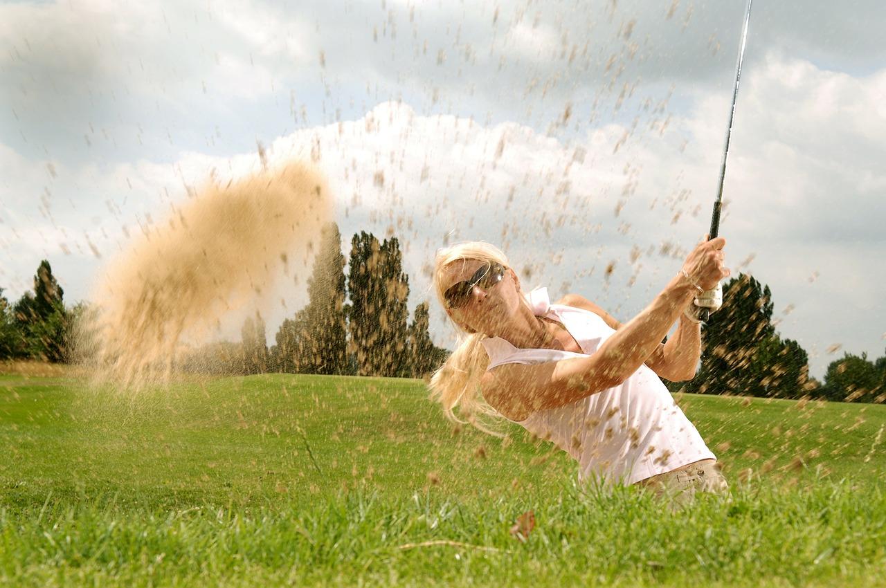 Golfen am Wolfgangsee: eine Golferin schlägt einen Ball in Richtung des Betrachters.