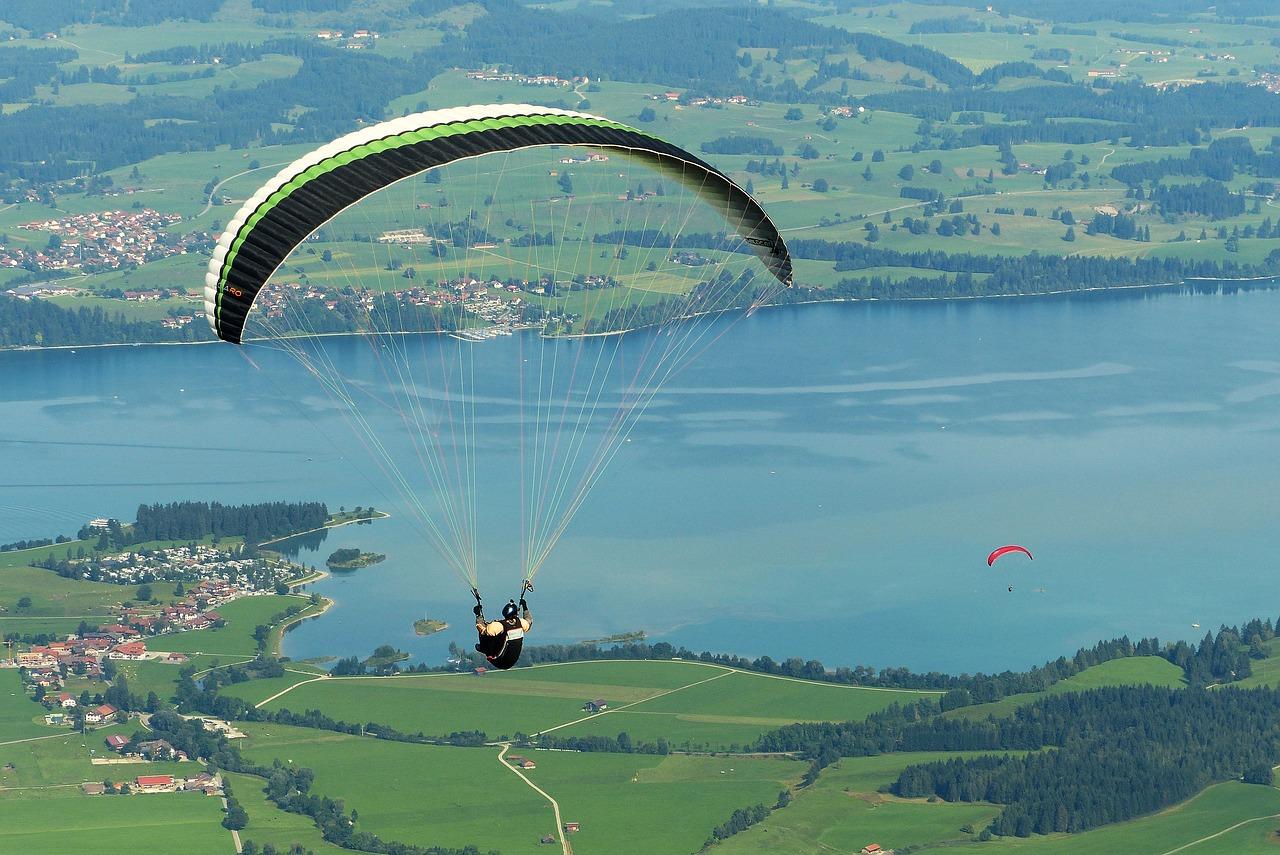 Paragleiten am Wolfgangsee: Ein Paragleiter mit dem Rücken zum Betrachter über dem See, von oben fotografiert.