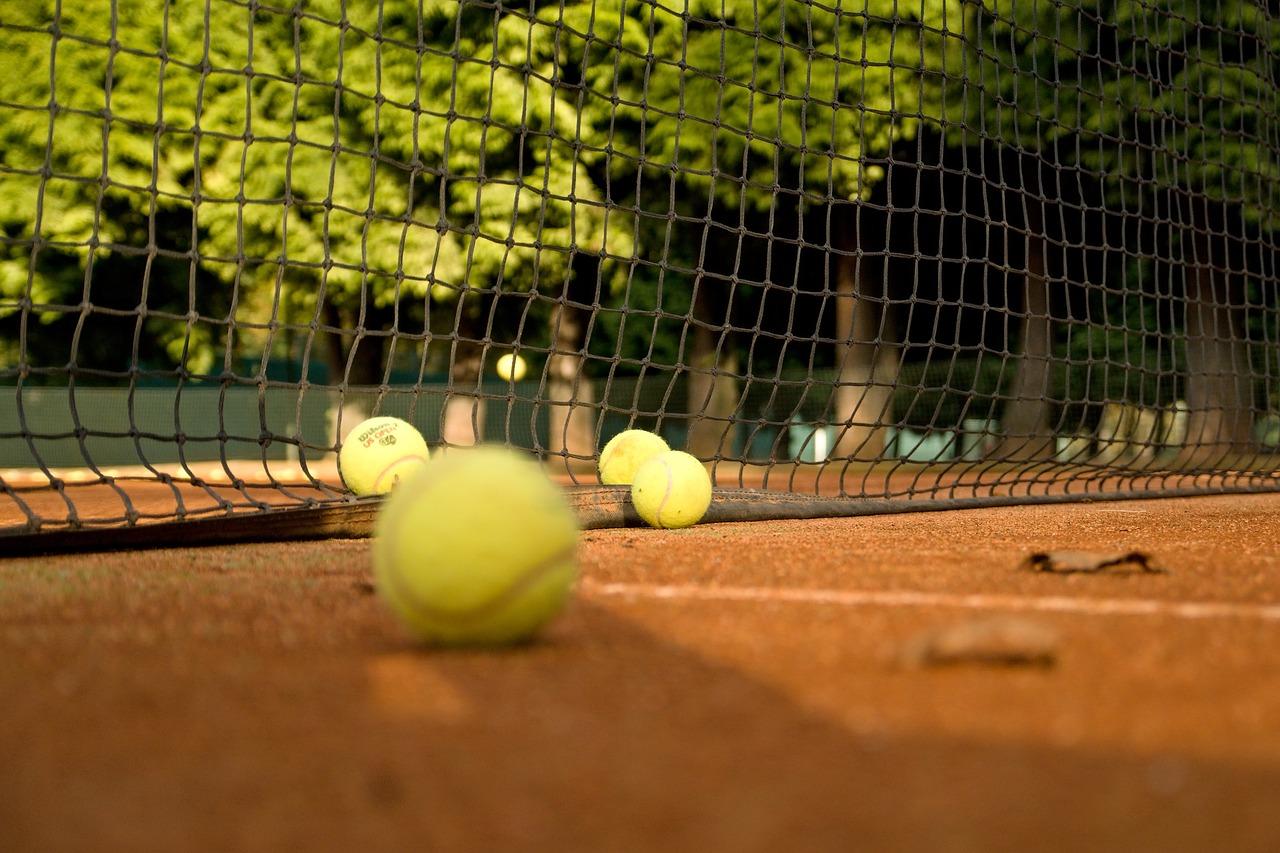 Tennis am Wolfgangsee: Einige Tennisbälle liegen am Boden vor dem Netz. Im Hintergrund ein Wald