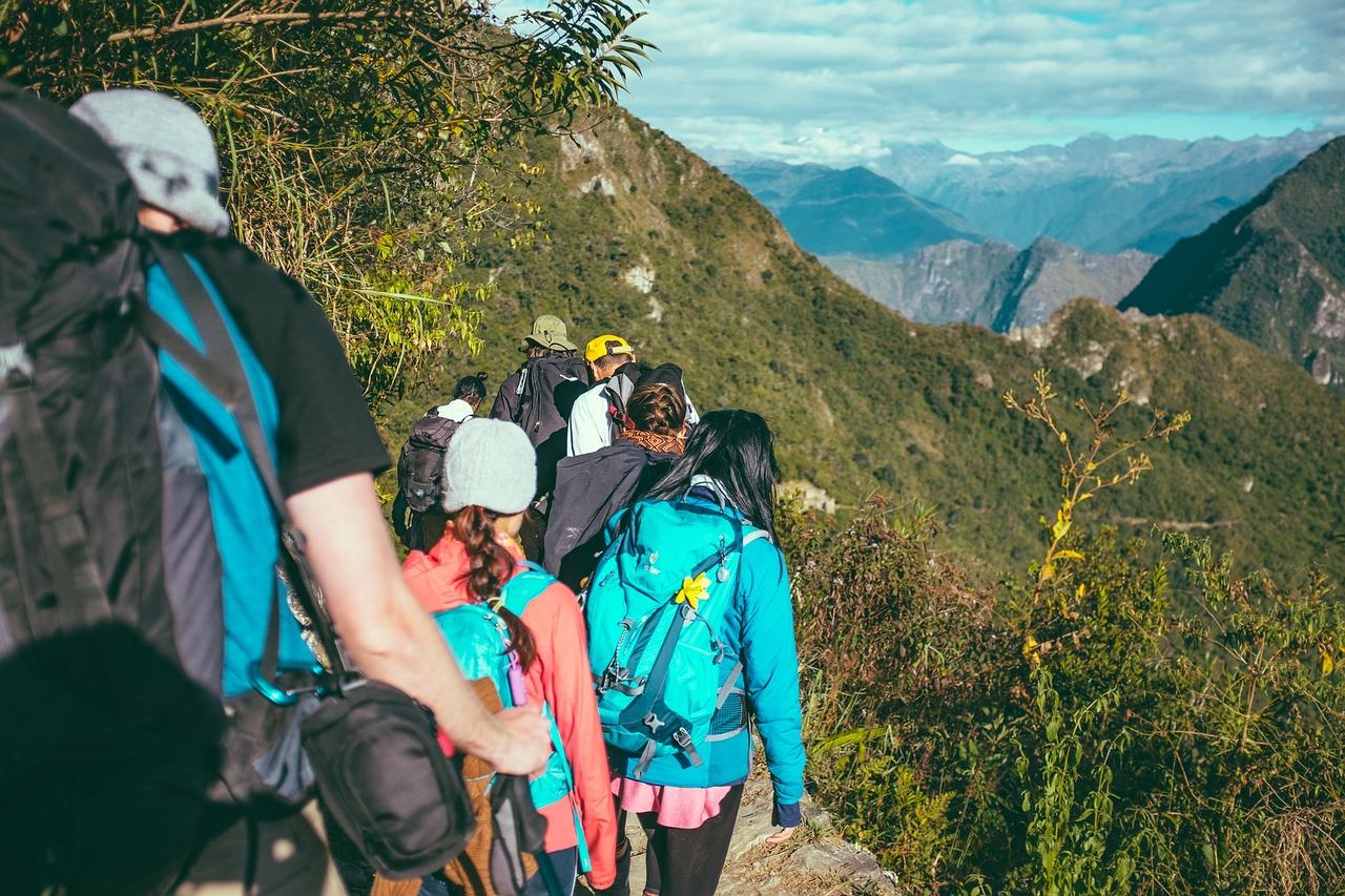 Wandern am Wolfgangsee: eine Gruppe von Wanderern im alpinen Bereich mit dem Rücken zum Betrachter. Im Hintergrund sommerliche alpine Almlandschaft.