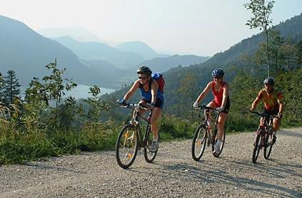 Radfahren am Wolfgangsee: im Vordergrund drei Radfahrer im Sommer; im Hintergrund alpine Berglandschaft, im Tal der Wolfgangsee