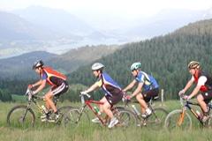 Radfahren am Wolfgangsee: vier Radfahrer in sommerlicher Landschaft, im Hintergrund Berge und der Wolfgangsee