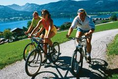 Radfahren am Wolfgangsee: drei erwachsene Radfahrer in sommerlicher Freizeitkleidungauf einem Schotterweg, im Hintergrund alpines Panorama und der Wolfgangsee