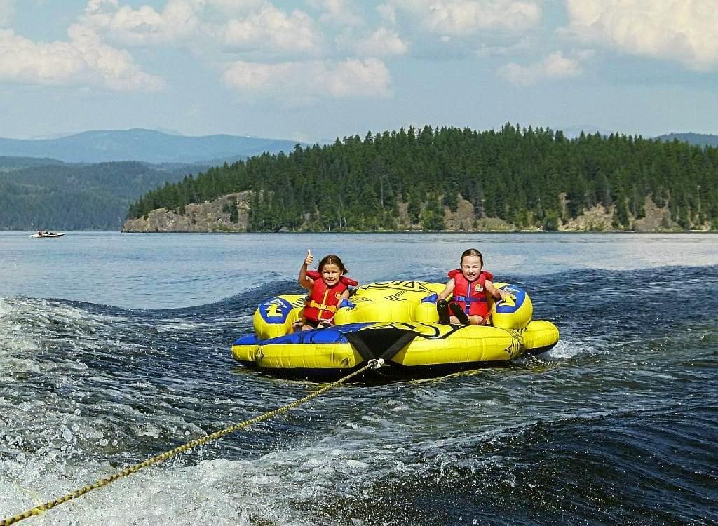 Wassersport am Wolfgangsee. im Vordergrund zwei Personen in je einem Schlauchboot auf dem See, das von einem Motorboot gezogen wird.
